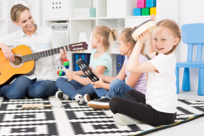 children playing instruments with a woman