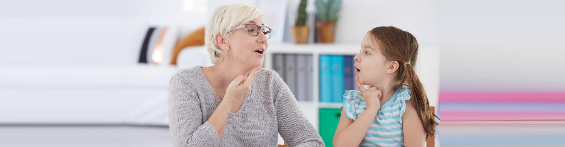 woman teaching a girl sign language